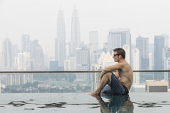 Young attractive man at the swimming pool in roof at skyscraper. Stock Photos