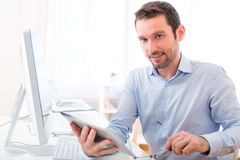 Young attractive man with tablet at the office. View of a Young attractive man with tablet at the office Stock Image