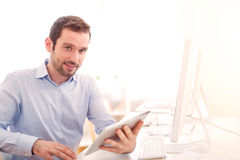 Young attractive man with tablet at the office. View ofa Young attractive man with tablet at the office Stock Photography