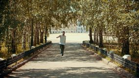 Young attractive man with tattoos dancing in the park on the path - buildings on the background. Mid shot stock footage