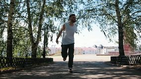 Young attractive man with tattoos freestyle dancing in the park - buildings on the background. Mid shot stock footage