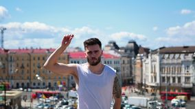 Young attractive man with tattoos freestyle dancing on the top point in the centre of the city - pointing at the camera. Mid shot stock video