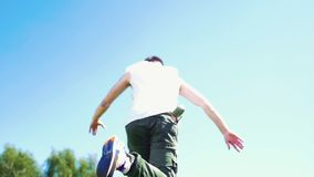 Young attractive man with tattoos freestyle dancing - walking upwards on the fresh green grass stock footage