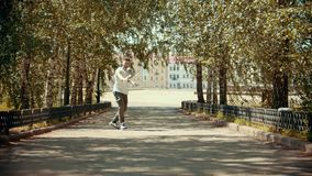 Young attractive man with tattoos performing locking dancing in the park and enjoying himself - buildings on the. Background. Mid shot stock video footage
