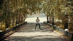 Young attractive man with tattoos performing locking dancing in the park on the path - buildings on the background. Mid shot stock footage