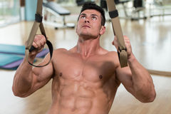 Young Attractive Man Training With Trx Fitness Straps Royalty Free Stock Photography