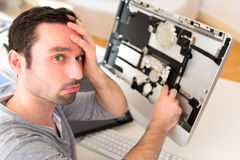 Young attractive man trying to repair computer Royalty Free Stock Photo