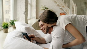Young attractive man using tablet computer lying in bed while his girlfriend come and hug him in bedroom at the morning stock footage