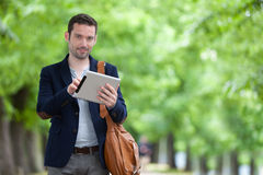 Young attractive man using tablet in Paris Royalty Free Stock Images