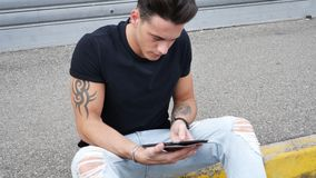 Young man using tablet PC outdoor in city. Young attractive man using tablet PC outdoor in city setting, in summer day stock video footage