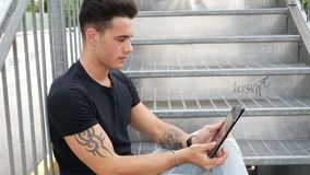 Young man using tablet PC outdoor in city. Young attractive man using tablet PC outdoor in city setting, in summer day stock footage