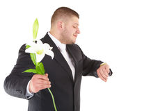 Young attractive man waiting with flowers orchids. Attractive  man with flower looks on watch. Isolated over white Stock Images