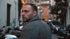Young attractive man walking in the side street. Male turns, looks around and smile. Enjoying the vacation in Europe. Guy exploring the new town stock footage