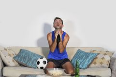 Young attractive man watching football game TV praying nervous a. Nd excited instress holding soccer ball drinking beer eating popcorn at home sofa couch in Royalty Free Stock Images