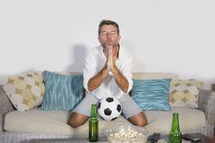Young attractive man watching football game TV praying nervous a. Nd excited instress holding soccer ball drinking beer eating popcorn at home sofa couch in Stock Photos