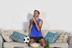 Young attractive man watching football game TV praying nervous a. Nd excited instress holding soccer ball drinking beer eating popcorn at home sofa couch in Royalty Free Stock Photography