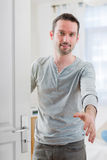 Young attractive man welcoming you in his house. View of a Young attractive man welcoming you in his house Stock Photography