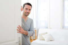 Young attractive man welcoming you in his house Royalty Free Stock Photos