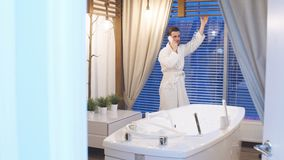 Young attractive man in white robe resting in a luxury Spa center. Man standing at the panoramic window and talking on a stock video footage