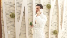 Young attractive man in white robe resting in a luxury Spa center. stock video