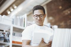 Young attractive man in white t-shirt smiling and reading book with blank cover. Stock Photo