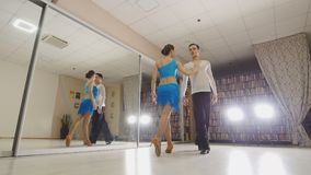 Young attractive man and woman dancing and practicing Latin dance in costumes in the Studio. Young attractive men and women dancing and practicing Latin dance in royalty free stock photo