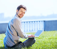 Young attractive man working on laptop outdoor Stock Image