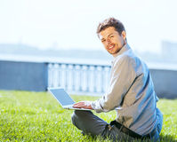 Young attractive man working on laptop outdoor Royalty Free Stock Images