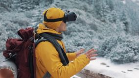Young attractive man in yellow jacket enjoying virtual reality glasses headset or 3d game outdoors at winter mountains. Technology, innovation, cyberspace and