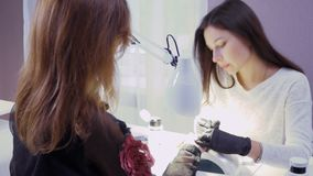 Manicurist makes manicure to young woman. Young attractive manicure master and client are in the cabinet. Young pretty lady wearing black gloves covers woman`s stock video footage