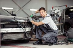 A young and attractive mechanic in a unifors is polishing an expensive car royalty free stock photo