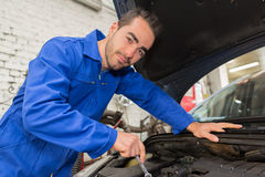 Young attractive mechanic working on a car at the garage Royalty Free Stock Image
