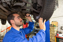 Young attractive mechanic working on a car at the garage Stock Image