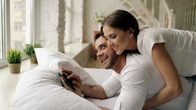 Young attractive man using tablet computer lying in bed while his girlfriend come and hug him in bedroom at the morning. Young attractive men using tablet Stock Images