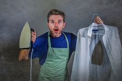 Young attractive messy and upset man in kitchen apron holding iron and burnt shirt with worried face expression in housework and d Royalty Free Stock Photos