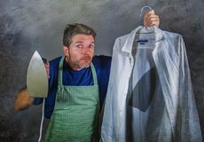 Young attractive messy and upset man in kitchen apron holding iron and burnt shirt with worried face expression in housework and d Stock Image