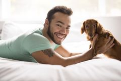 Young attractive mexican man at home lay on bed with teckel dog stock image