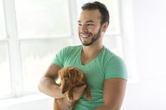 Young attractive mexican man at home with teckel dog stock photography