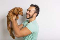 Young attractive mexican man at home with teckel dog royalty free stock photography
