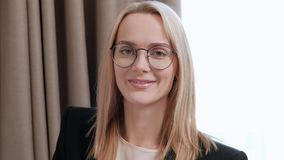 Young attractive middle-aged blonde woman in a black business suit and eyeglasses in a hotel room. Writes messages on stock video footage