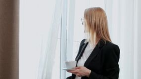 Young attractive middle-aged blonde woman in a black business suit and glasses in a hotel room. Stands by the window stock video