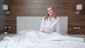 Young attractive middle-aged blonde woman in a white coat wakes up in the morning in bed. stock video footage