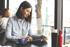 Happy young woman drinking cappuccino, latte, macchiato, tea, using tablet computer and talking on the phone in a coffee shop / ba royalty free stock photos