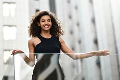 Smiling young mixed-race woman at the street royalty free stock photos