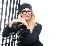 Young attractive model rests against camera onto. Backstage relaxation. Young appealing female model leans on tripod camera while sitting royalty free stock images