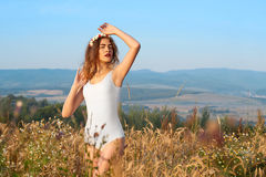 A young, attractive model in swimsuit, posing in a field of flow. Ers and wheat on a background of blue sky, hair, makeup, white corolla with flowers, model is Stock Photography