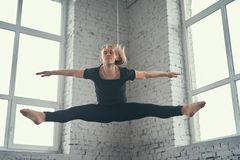 The young attractive modern ballet dancer in black jacket. Jumping over urban background royalty free stock images