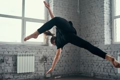 The young attractive modern ballet dancer in black jacket. Jumping over urban background royalty free stock photography