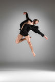 The young attractive modern ballet dancer jumping. The young attractive modern ballet dancer in black jacket  jumping over gray background Royalty Free Stock Photos