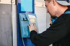 Young attractive modern man talking on the payphone Royalty Free Stock Photography